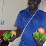 Etienne shows fruits and vegetables from the first harvest since the hurricane